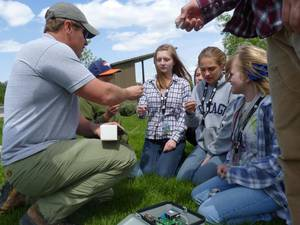 An adult 4-H volunteer showing youth macroinvertebrates from a freshwater stream.