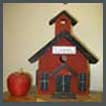 red apple and red model of an old single room school